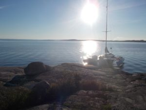 Shows the boat moored up at a rocky island in Sweden